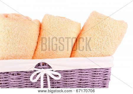 Color towels in wicket basket, isolated on white