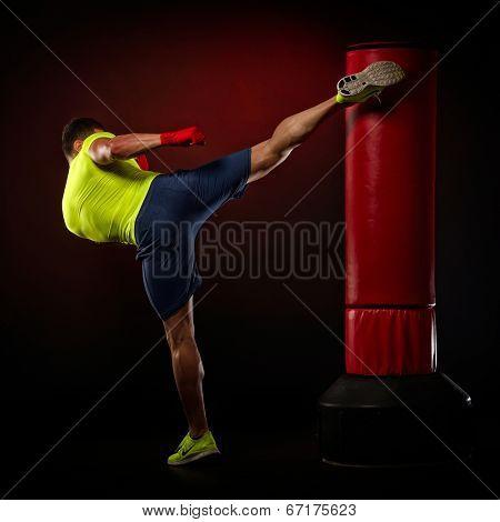 young man exercising bag boxing in studio