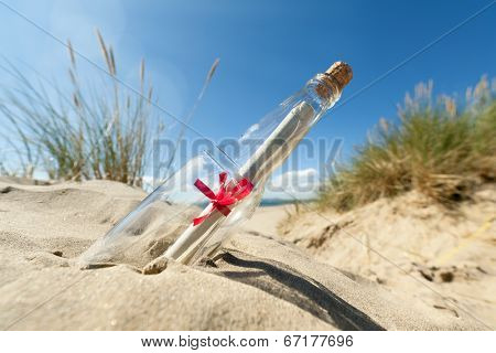 Message in a clear glass bottle washed up on the beach concept for sos, assistance, help and stranded