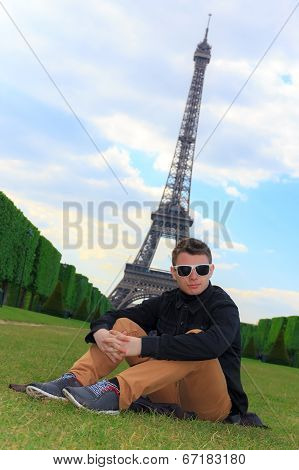 Young Man Hipster Sitting Near The Eiffel Tower, France