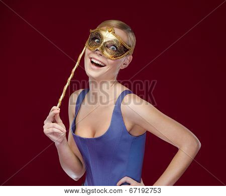 Young woman with masquerade masque, isolated on purple