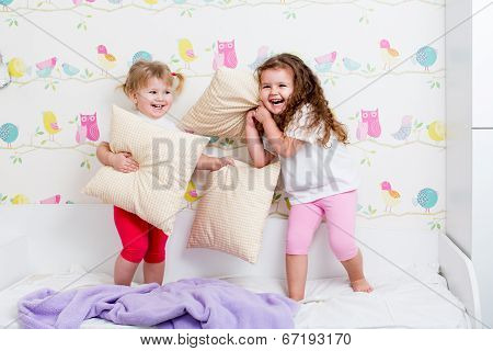 Children Sisters Playing On The Bed Indoors