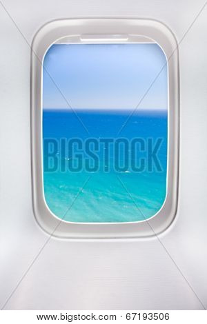 side window of airplane with sea view