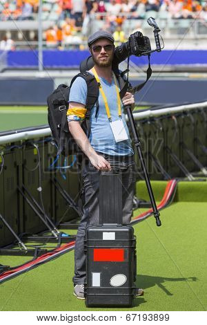 A sports photographer posing along a sportsfield with his camera on his shoulder with a monopod mounded on it, in his other hand he hold a case for the other lenses.