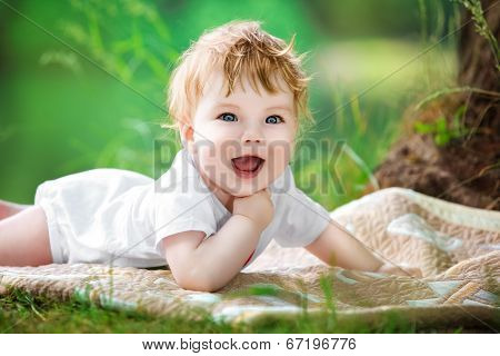 Happy Little Baby Having Fun In The Park On The Lake Shore Background. Summer Vacations Concept.
