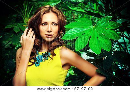 Attractive young woman  among the tropical plants. Vacation. Tropics. Fashion shot.
