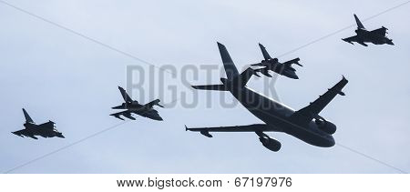 BERLIN, GERMANY - MAY 21, 2014: Airbus A310-304 is used as a tanker and fly two Tornado in refueling position, two outside flying Eurofighter are in waiting position, demonstration at ILA Air Show.