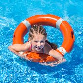 stock photo of lifeline  - smiling cute  girl swims with a lifeline in the pool in  summer - JPG