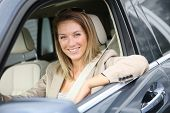 picture of 35 to 40 year olds  - Cheerful woman at car window driving brand new vehicle - JPG