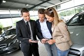stock photo of 35 to 40 year olds  - Couple in car dealership looking at brochure with salesman - JPG