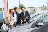 stock photo of 35 to 40 year olds  - Car dealer showing vehicles to couple  - JPG