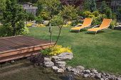 stock photo of lawn chair  - A pair of bright yellow designer lawn chairs invite you to relax in this beautifully landscaped backyard with deck spanning a creek in the foreground - JPG