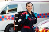 pic of paramedic  - beautiful young female paramedic carrying lifepack in front of ambulance - JPG