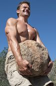 stock photo of struggle  - Strong muscular shirtless Caucasian man struggles to carry heavy boulder in rural countryside environment - JPG