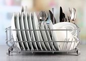 stock photo of crockery  - Clean dishes drying on metal dish rack on light background - JPG