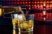 image of liquor bottle  - barman pouring whiskey in a lounge bar on wood table - JPG