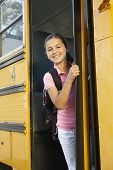 foto of pre-teen girl  - Pre teen girl getting on school bus - JPG