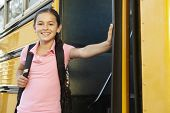 stock photo of pre-teen girl  - Pre teen girl getting on school bus - JPG