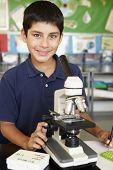 foto of pre-teen boy  - Boy in science class with microscope - JPG