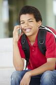 stock photo of pre-teen boy  - Pre teen boy with phone at school - JPG