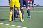 picture of encounter  - Hockey players from two different teams guarding during a match on an artificial grass pitch - JPG
