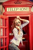 picture of phone-booth  - Pretty young woman talking on the phone in telephone booth - JPG