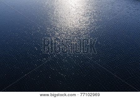 reflections of sun in deep blue water