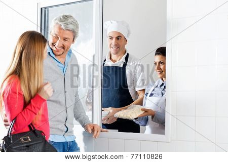 Happy male and female chefs selling uncooked pasta packet to couple