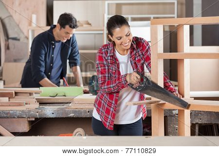 Happy female carpenter cutting wood with handsaw while colleague working in background at workshop