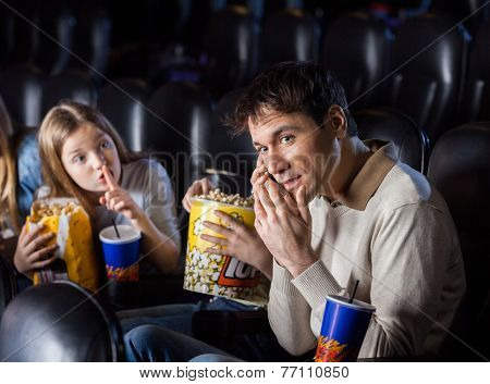 Angry daughter giving shh expression to father using mobilephone in movie theater