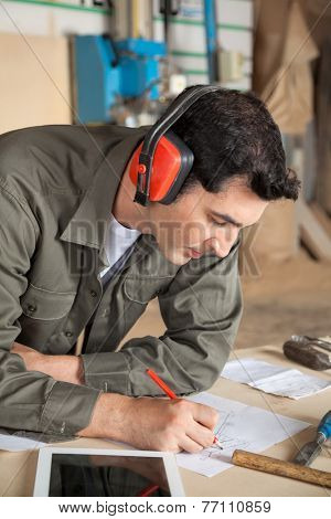 Young carpenter working on blueprint while wearing ear protectors at table in workshop