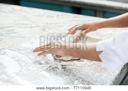 Cropped image of female chef's hands rolling dough at messy counter in commercial kitchen