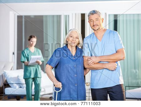 Portrait of confident male caretaker and disabled senior woman with female nurse in background at nursing home yard