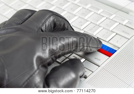 Hacking Russia Concept With Hand Wearing Black Leather Glove Pressing Enter Key With Flag Overlaid