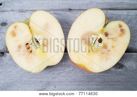 Spoiled Apple Cut In Two Half On Wooden Background