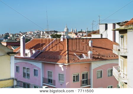 Top Of Pink Apartment With City In Behind