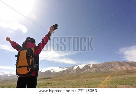woman cheering at mountain peak in tibet,china