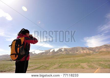 woman photographer taking photo at mountain peak in tibet,china