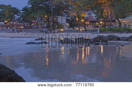 Light of lanterns reflects in the sea surf. Thailand, Phuket, Kata Beach