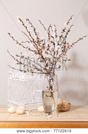 Easter still-life with a blossoming branch, eggs and a white cage