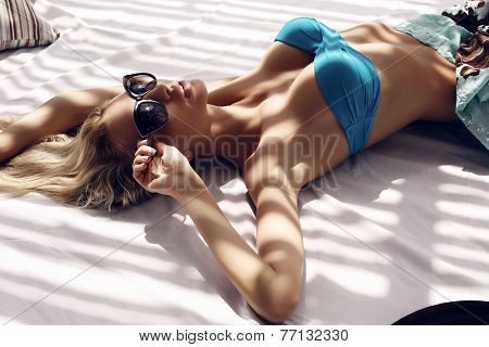 Sexy Woman With Blond Hair In Bikini And Sunglasses Relaxing On Beach