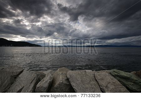 Fjord landscape of dramatic sky, stones and sea