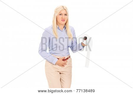 Young woman in need to pee holding a toilet paper isolated on white background