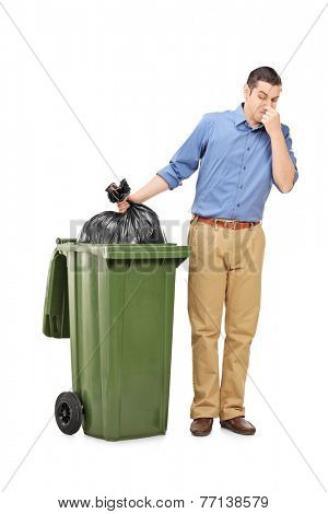Full length portrait of a man throwing out a stinky bag of trash isolated on white background