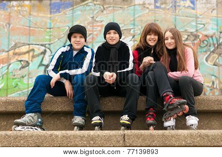 Group of happy teenagers having fun in roller skates