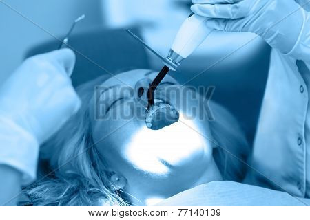 Dentist Curing A Female Patient