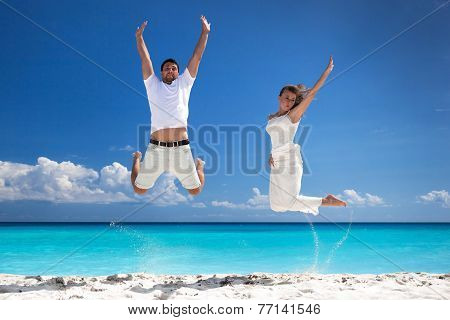 Happy Newlyweds Jumping Up On Beach