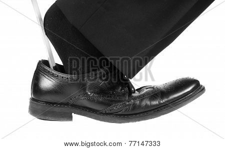 Person Entering Foot Into Black Leather Shoe With Shoehorn