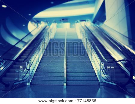stairs and an escalator at an airport toned with a retro vintage instagram filter effect