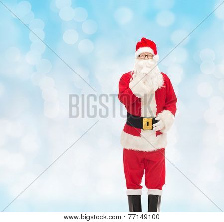 christmas, holidays and people concept - man in costume of santa claus making hush gesture over blue lights background